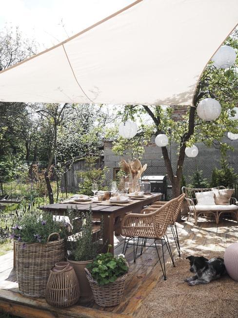 Drewniany stół w ogrodzie, obok lawendy w koszach