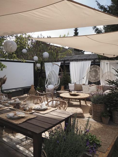 Przytulny taras w ogrodzie Marideko z lampionami i kinem pod chmurką.
