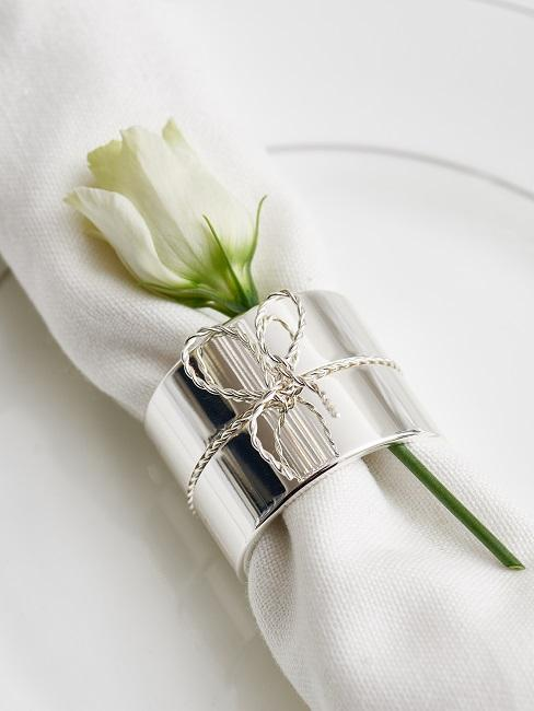 Biała serweta wraz ze srebrna obręczą do serwetki oraz różą