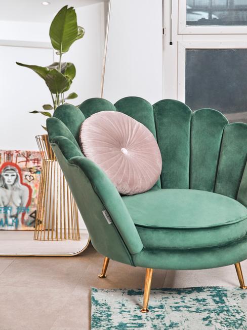 Fragment salonu z zielonym fotelem w kształcie muszelki oraz różową poduszką