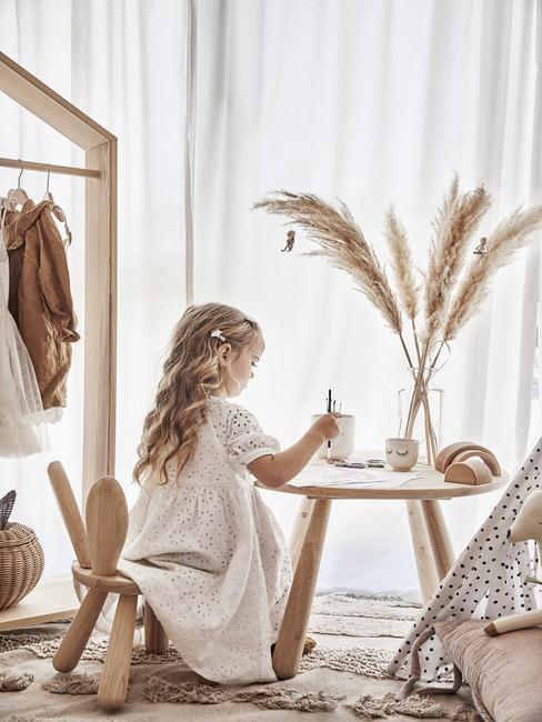 Wnętrza Montessori. Rysująca dziewczynka przy stole