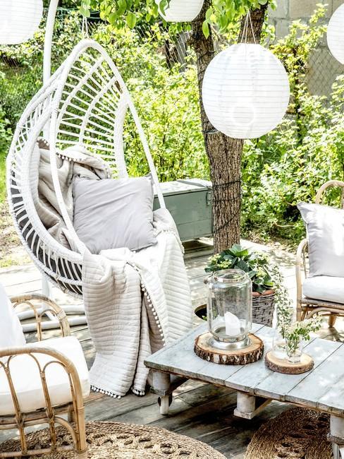 Fragment ogrodu z huśtawką, lampionami oraz meblami ogrodowymi wykonany z palet