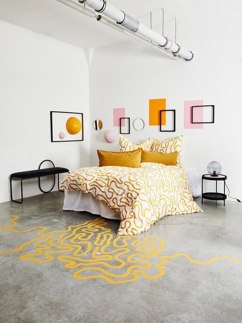 Biała sypialnia w loficie z kolorowymi ramkami na ścianie i pościelom