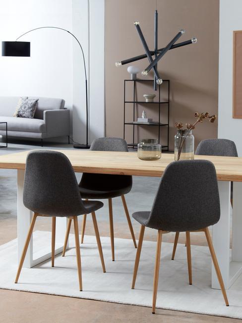 Jadalnia połączona z salonem, z jasnym, drewnianym sotłem, ciemnymi krzesłami oraz metalową szafką