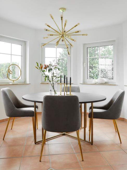 Jadalnia z okrągłym stołem, szarymi krzesłami oraz złotą lampą