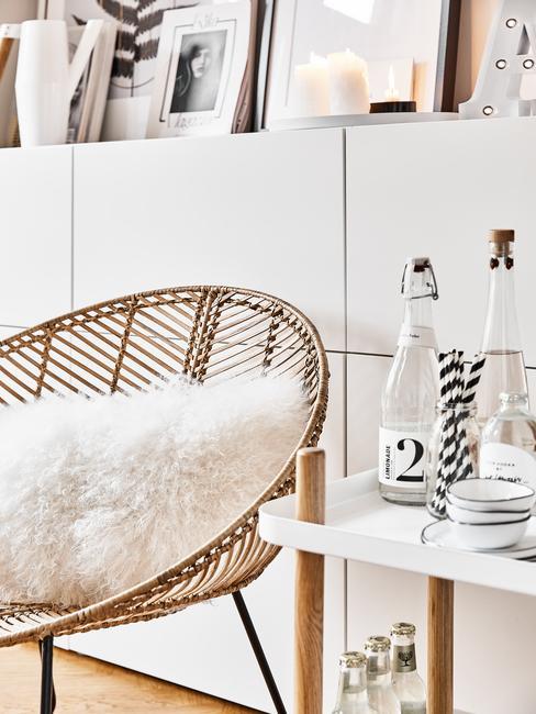 Fragment białego salonu z rattanowym krzesłem, poduszka, barkiem oraz białą szafką