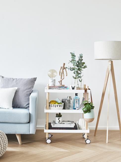 Fragment niebieskiej sofy, barek na kółkach oraz lampą