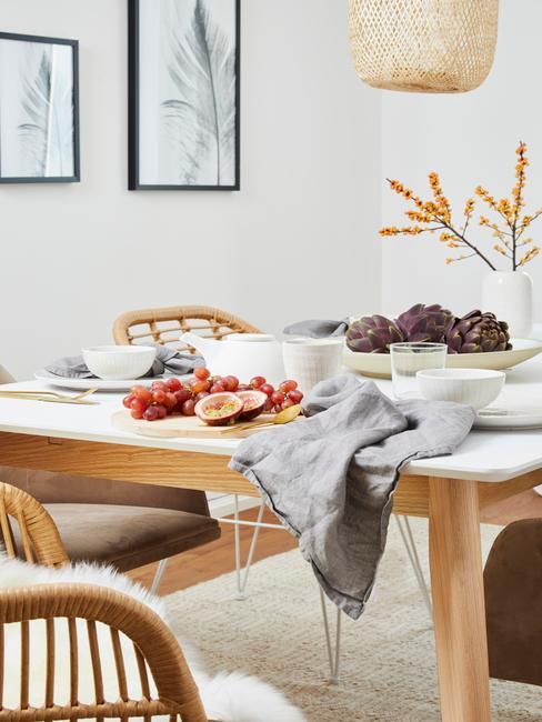 Biała jadalnia z drewnianym stołem, różnymi krzesłami oraz dekoracjami