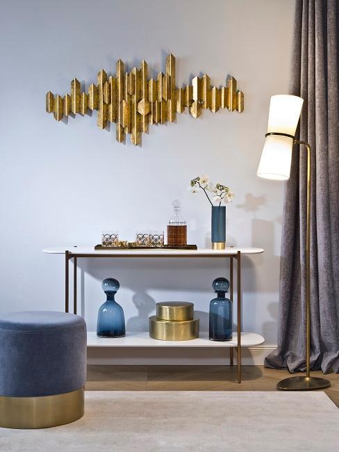 Fragment pomieszczenia z niebieskim pufem z aksamitu i dwupoziomową, białą półką i złotą dekoracją na ścianie