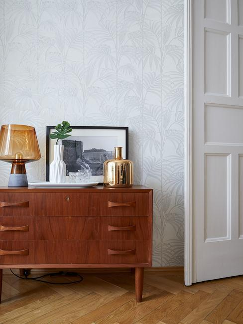 Fragment pomieszczenie z tapetą na ścianie i ciemną komodą w stylu retro oraz dekoracjami