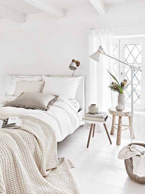 Biała sypialnia z łożkiem, drewnianym stolikiem nocnym, lampą praz dekoracjami