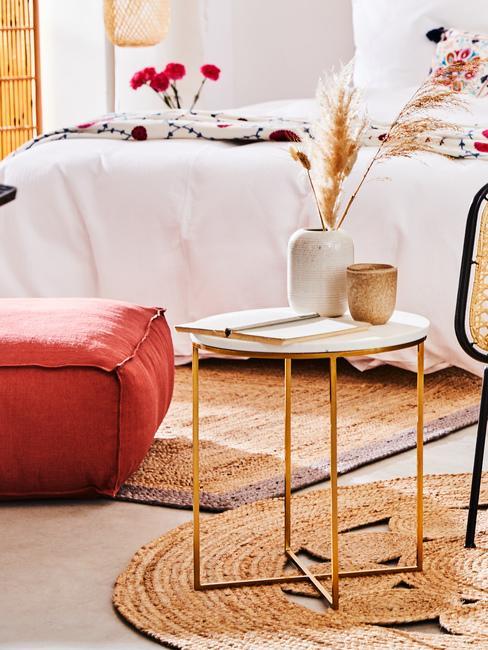 Fragment pomieszczenia z pufem, metalowym stolikiem kawowym na krótym znajduje się wazon oraz kubek z kamionki