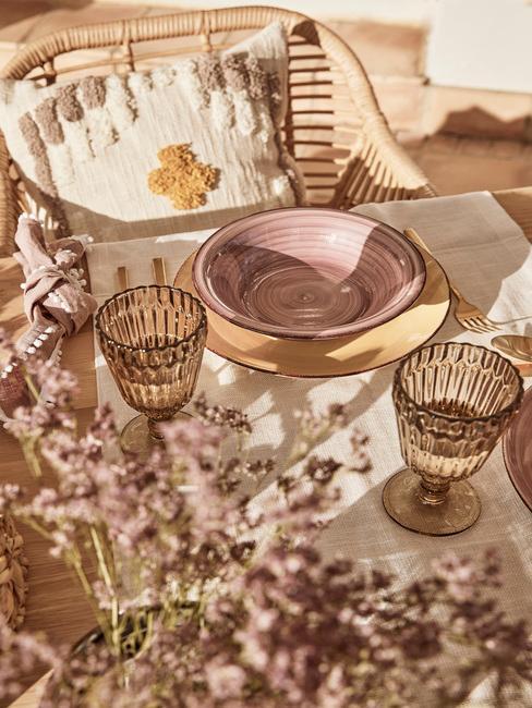 zbliżenie na zastawę z kamionki w różowym kolorze na stole na tarasie przy bursztynowych kieliszkach