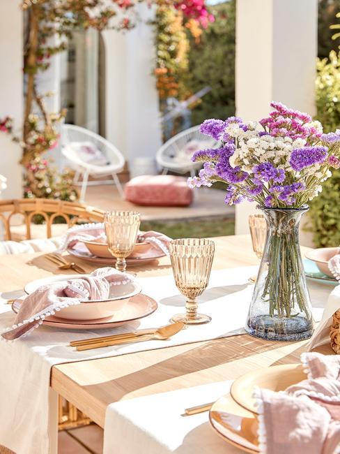 stół na tarasie z bukietem fioletowych kwiatów i zastawą w odcieniach różu i kryształowymi kieliszkami w ciepłym kolorze