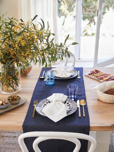 drewniany stół do jadalni z granatowym bieżnikiem i zastawą w bieli i wgranacie oraz ze złotymi sztućcami
