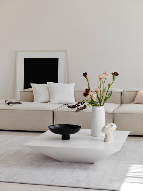 Jasny salon z beżową sofą, stolikiem z wazonem z kamionki