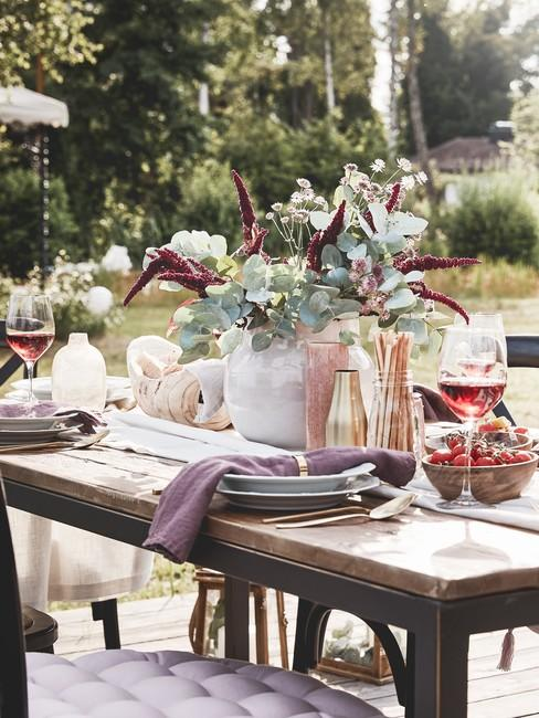 Drewniany stół z zastawą, wazonem kwiatów oraz dekoracjami