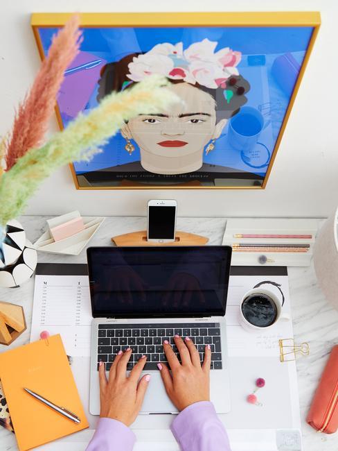 Osoba pracująca przy biurku nad któym wisi plakat Fridy Khalo