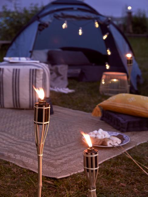 Zbliżenie na niebieski namiot udekorowany girlanda świetlną weraz z dywanem, pufem oraz poduszkami