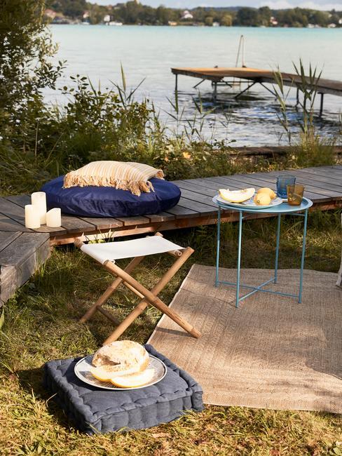 Zbliżenie na miejsca do siedzienie oraz dywan nad jeziorem