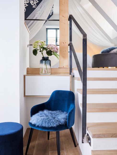 Sypialnia znajdująca się na poddaszu do której prowadzą schody obok których stoi niebieski fotel