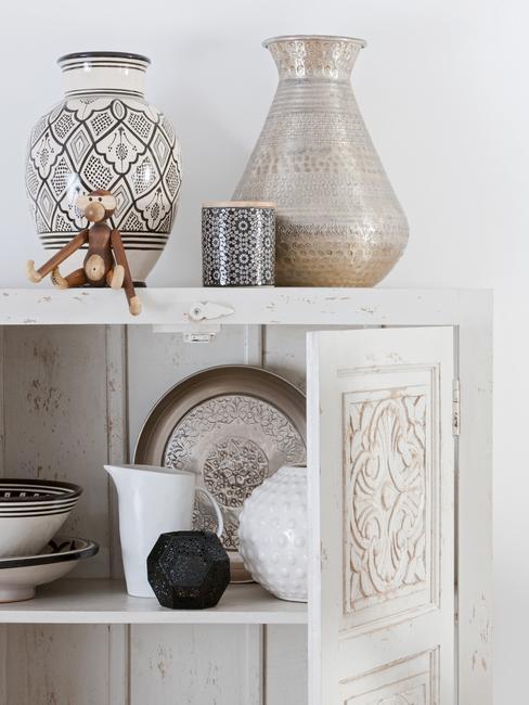 Biała szafa z ceramiką ułożoną na półce
