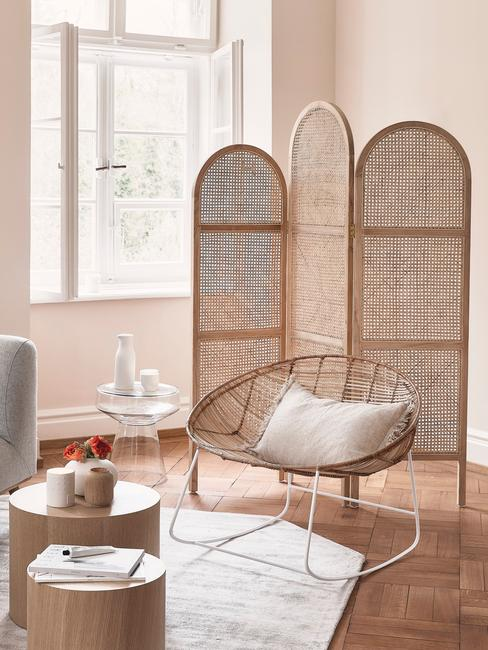 fragment salonu w stylu boho z rattanowym parawanem, krzeslem z poduszka oraz stolikiem