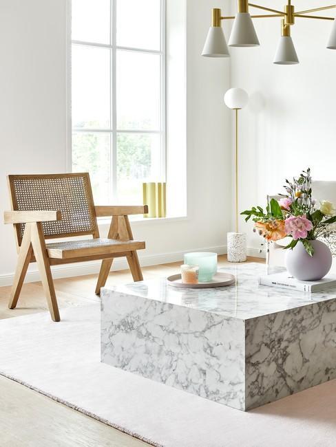 Fragment salonu z rattanowym krzesłem oraz marmurowym stolikiem kawowym, na którym znajduje się wazon z kawiamia
