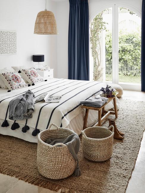 Rattanowe kosze stojące przy łóżku w sypialni