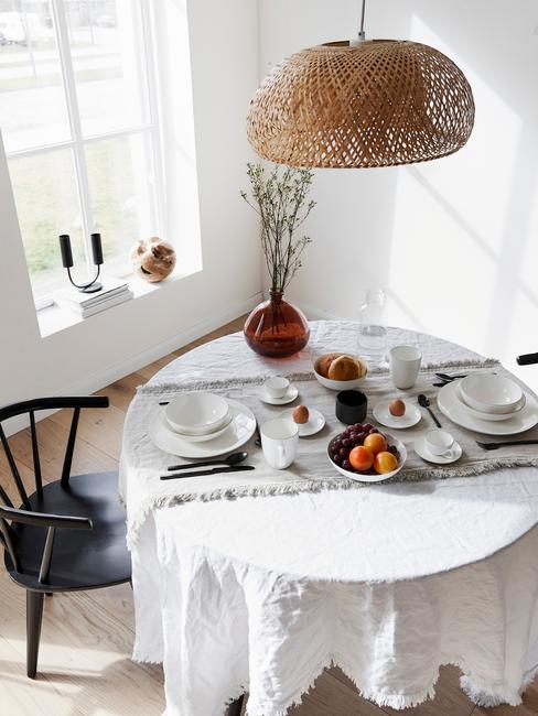 Rattanowy abażur wiszący nad stołem z białą serwetą