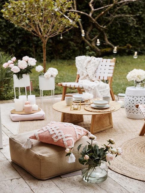 Drewniany taras z pufem, rattanowym krzesłem, drewnianym stolikiem, doniczkami z kwiatami