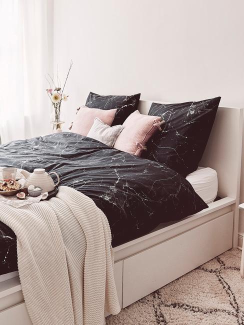 Biała sypialnia z dużym łożkiem z czarną pościelą we wzór marmurowy
