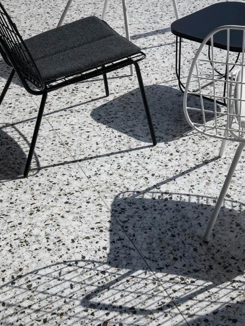 Zbliżenie na podłogę na tarasie wykonaną z lastriko, na której są ustawione krzesła