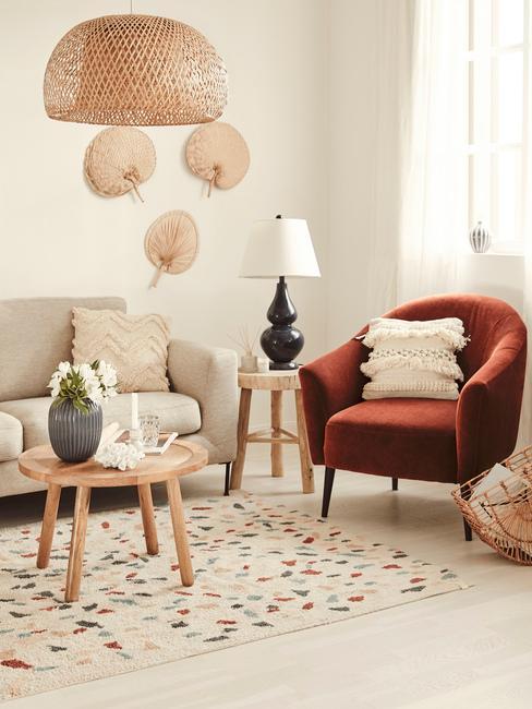 Salon boho z beżową sofą, pomarańczowym sotelem, drewnianym stolikiem i dywanem z motywm terazzo