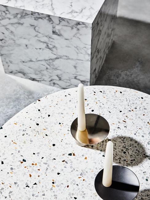 Zbliżenie na stolik kawowy z motywam lastriko ze świacami oraz fragment marmurowego stolika