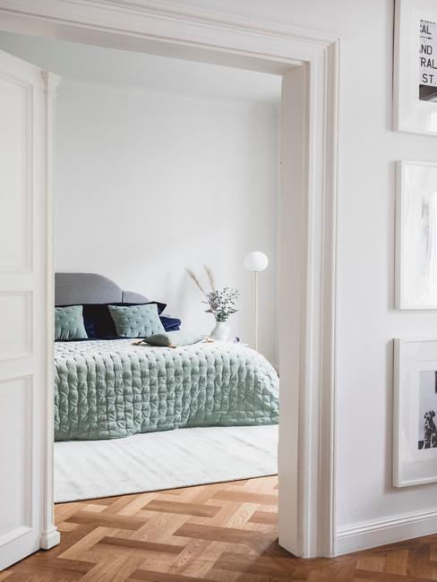 Biała sypialnia z łożkiem o akamitej narzucie