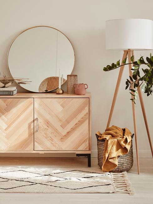 Salon z jasną, drewnianą komodą, lustrem, dywanem, koszem z juty oraz lampą