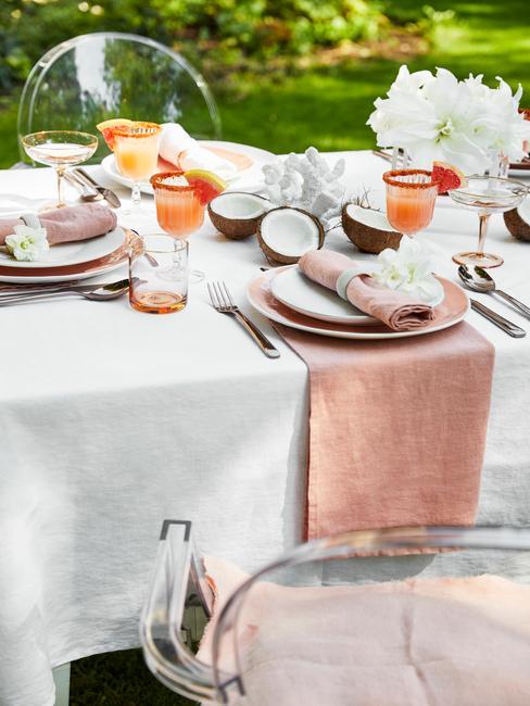 Zastawiony stół w ogrodzie na przyjęcie letnie oraz krzesłą wykonane z plexi