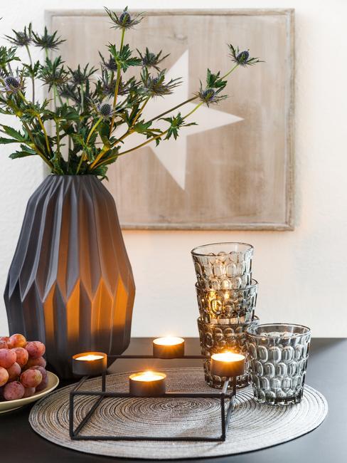 Zbliżenie na ceramiczny wazon z kwiatami, świeczki z świeczniki oraz szklanki z przydymionego szkła