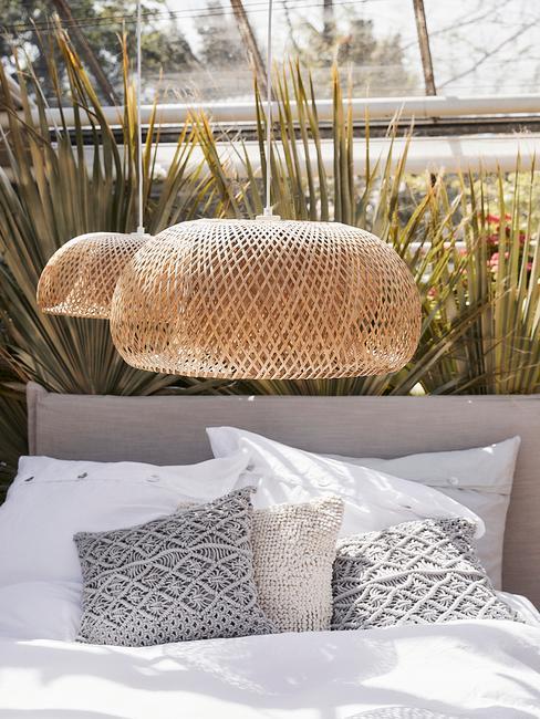Szare łóżko nad którym wiszą dwa, plecone abażury
