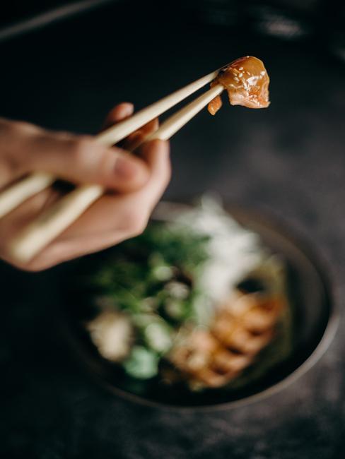 Osoba jedząca sushi pałeczkami
