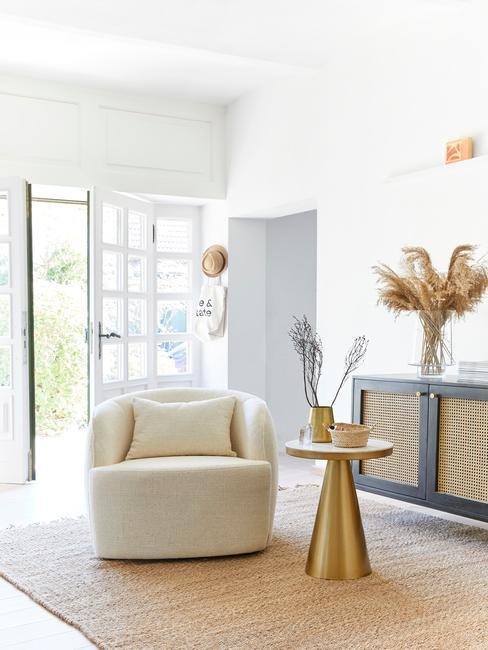 Biały salon z beżowym fotelem, złotym stolikiem oraz jutowym dywanem