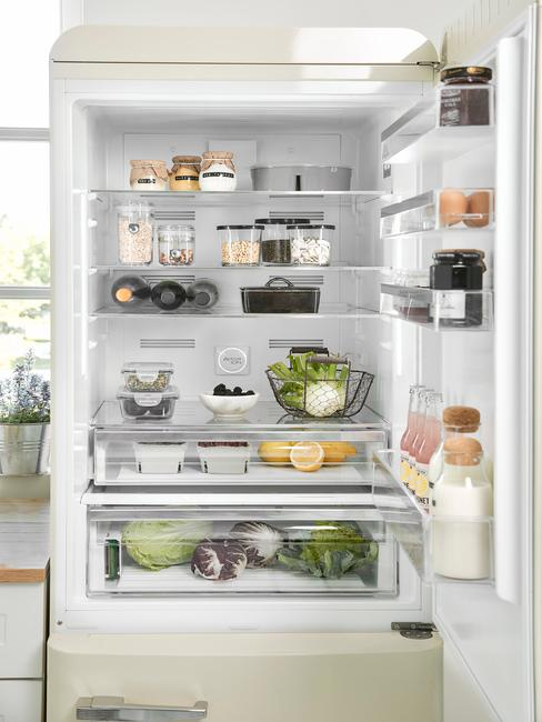 Otworzona lodówka z żywnością ułożoną na odpowiednich półkach