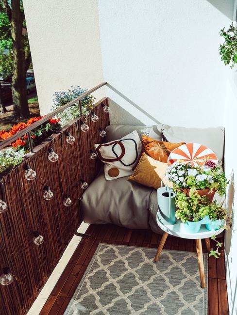Mała kanapa pokryta szarą narzutą z poduszkami, stolik z roślinami na balkonie w bloku
