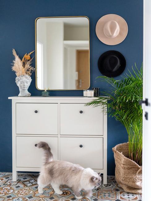 Przedpokój z niebieską ścianą, białą komoda oraz podłogą w płytki