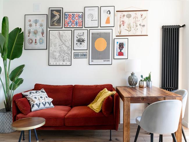 Salon połączony z jadalnią: czerwona sofa, drewniany stół oraz galeria obrazków na ścianie
