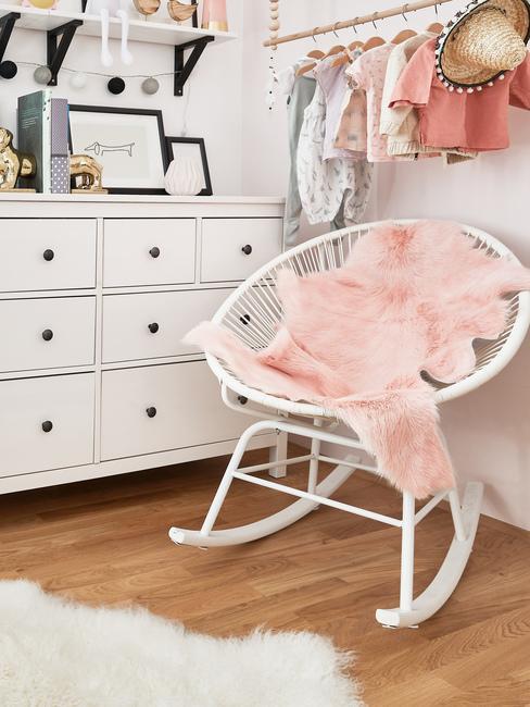 Fragment pokoju dziecięcego dla dziewczynki z fotelem, białą komodą oraz ubrankami na wieszakach