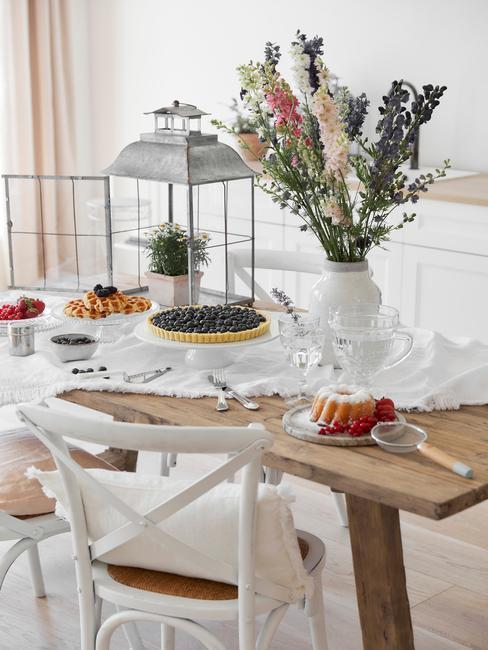 Drewniany stół z białym obrusem oraz krzesłami wraz z wazonem kwiatów oraz jedzeniem w stylu rustyklalnym