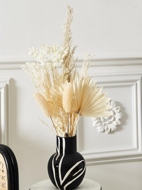 Białe pomieszczenie z kompozycją z jasnych, suszonych kwiatów w czarnym wazonie