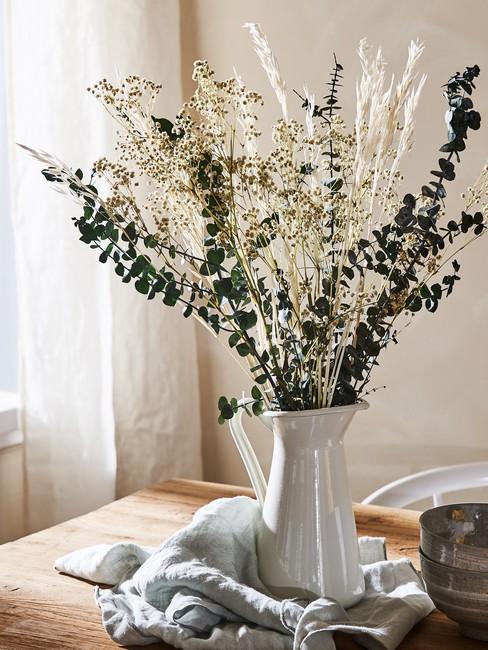 Drewniany stół z ceramicznym dzbankiem, w którym jest umieszczona kompozycja z suszonych kwiatów
